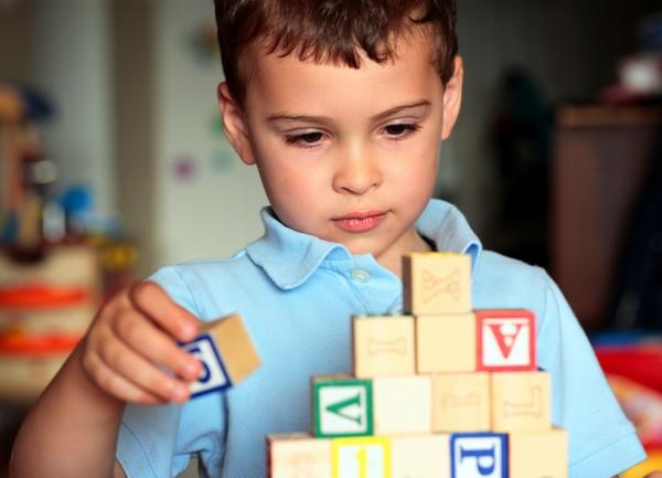 мальчик складывает кубики