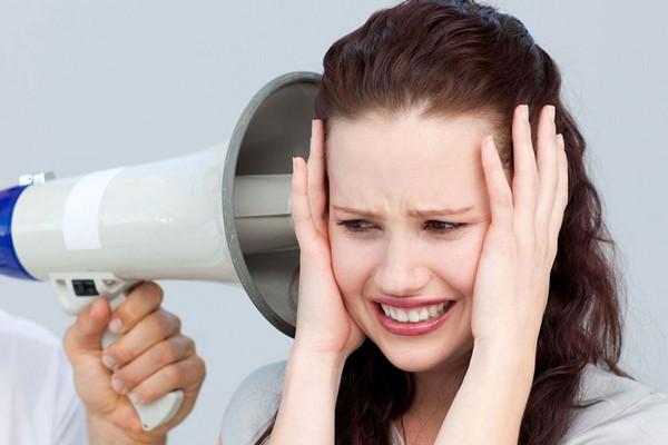 женщина закрыла уши руками